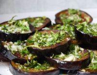 Оригинальное блюдо летнее-весеннего меню: запеченные с чесноком и сыром кружочки баклажанов с зеленью по-итальянски